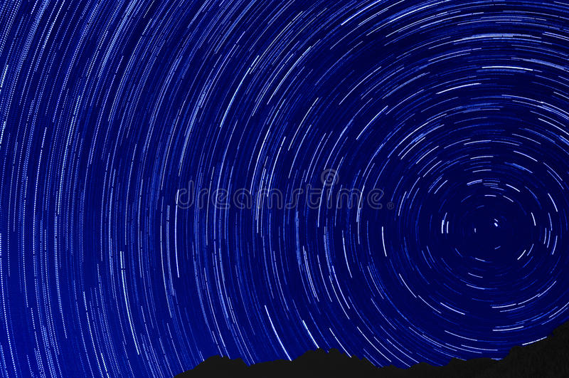 Star trail effect over mountain night sky. Colorful lights royalty free stock photos