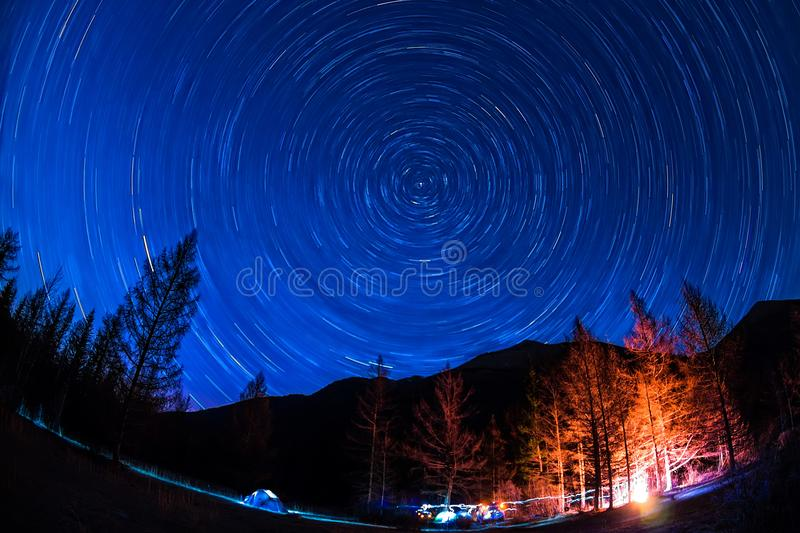 Star Trail in sky above the mountains fire in the tent camp royalty free stock image