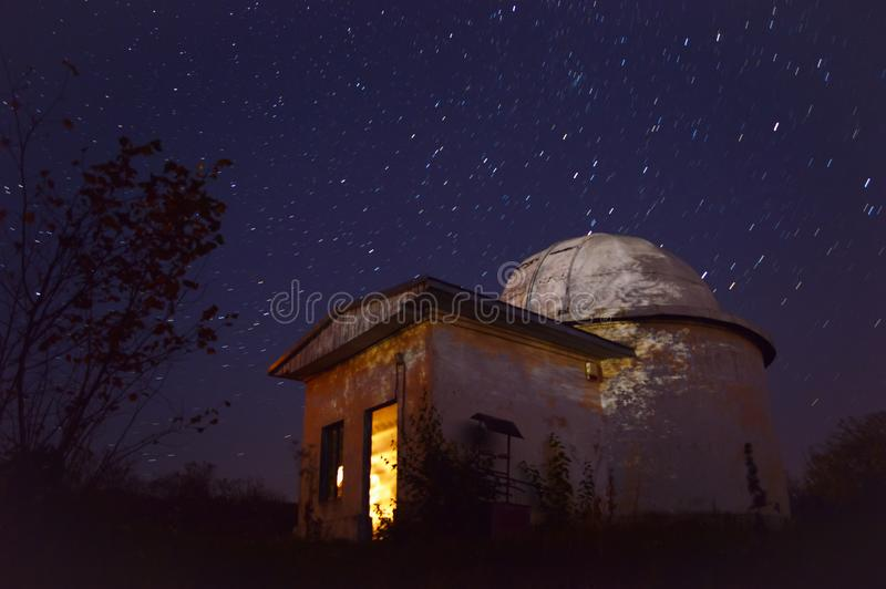 Star trails behind a telescope royalty free stock images