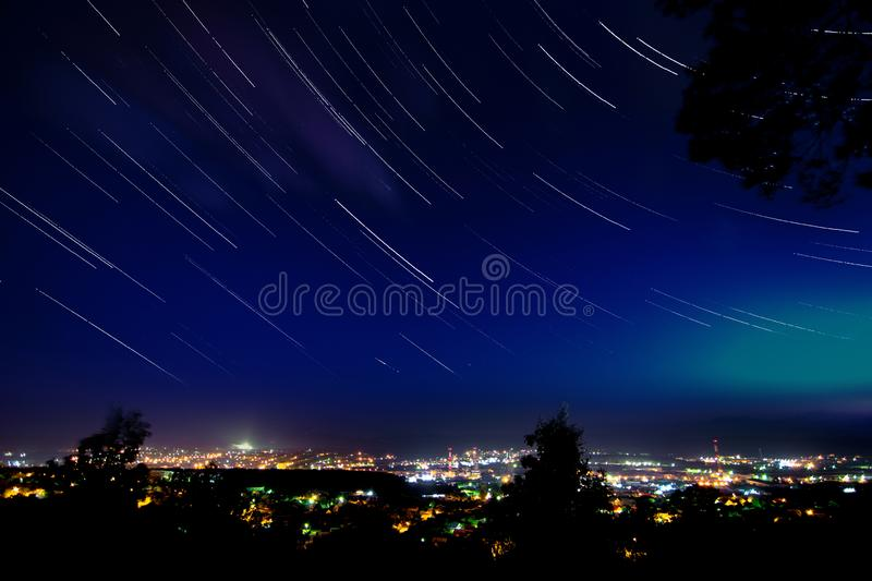 Star trails in clear night sky above the city with many lights stock images