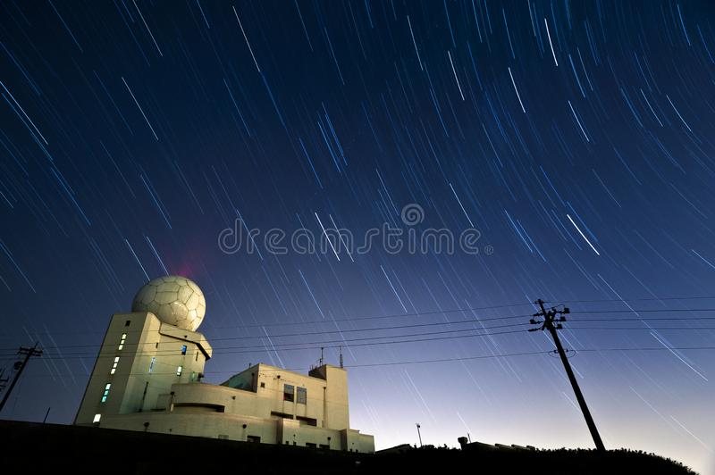 Star trails hovering above a weather radar station. On the peak of a mountain stock images