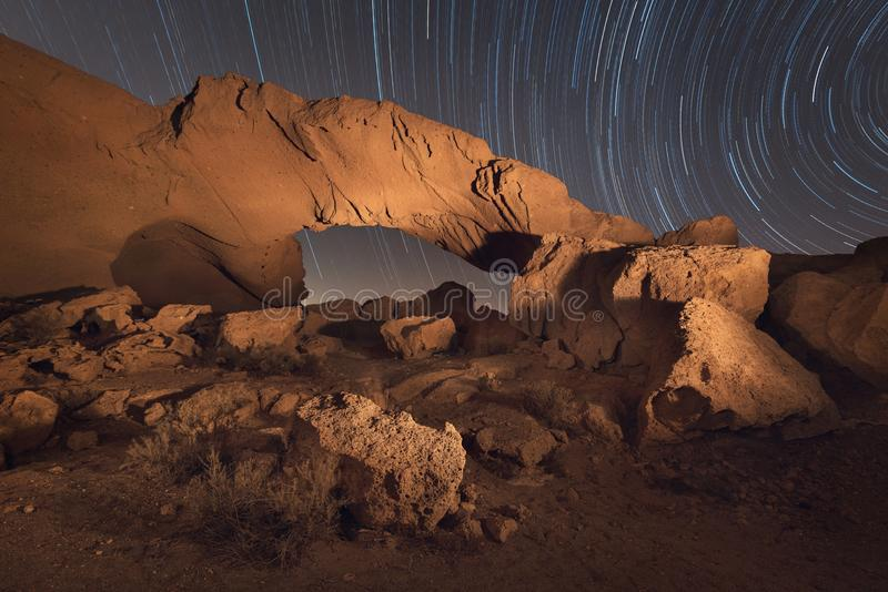 Star trails night landscape of a volcanic Rock arch in Tenerife, Canary island, Spain. royalty free stock photography