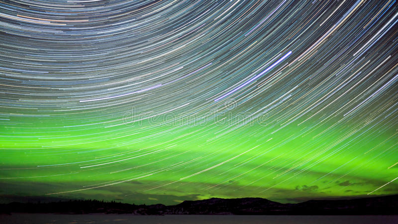Star trails and Northern lights in night sky stock image