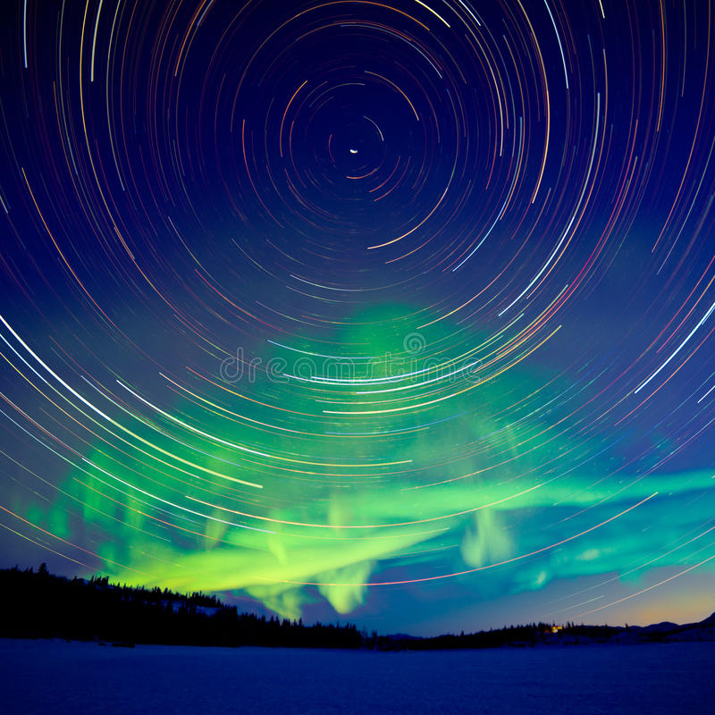 Star trails and Northern lights in night sky stock images