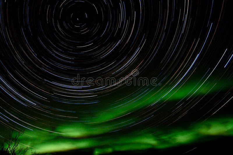 Star trails and Northern lights in night sky royalty free stock photo