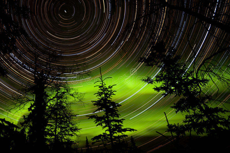 Star trails and Northern lights in sky over taiga stock photos