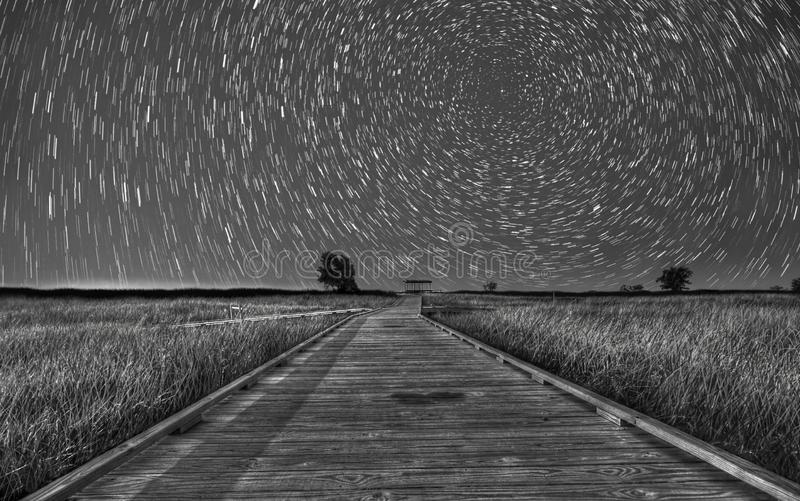 Star Trails over Headlands Beach, Ohio. A black and white rendition of star trails over the wooden walkway at Headlands Beach, Ohio. This walkway traverses royalty free stock photography