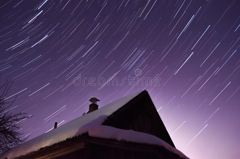 Star trails over the house late at night, purple night sky,. Snow on the roof of the house, winter night royalty free stock photo