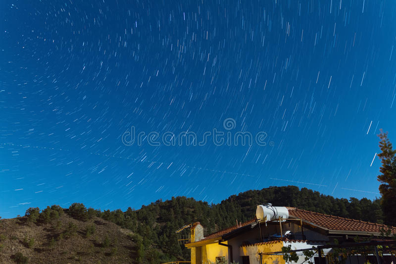 Star Trails over a house at the Troodos mountains. stock photo