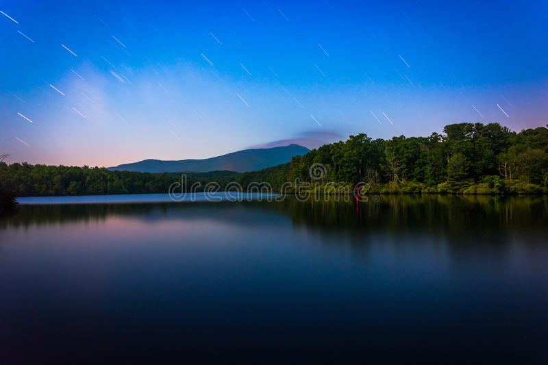 Star trails over Julian Price Lake at night, along the Blue Ridge Parkway in North Carolina. royalty free stock photo
