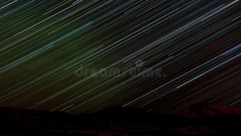 Star trails in sky over dark Yukon taiga landscape stock images