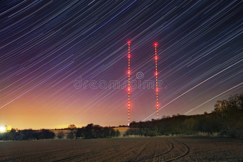Star trails with transmitter towers in winter night. Starry sky with red lights. royalty free stock photography