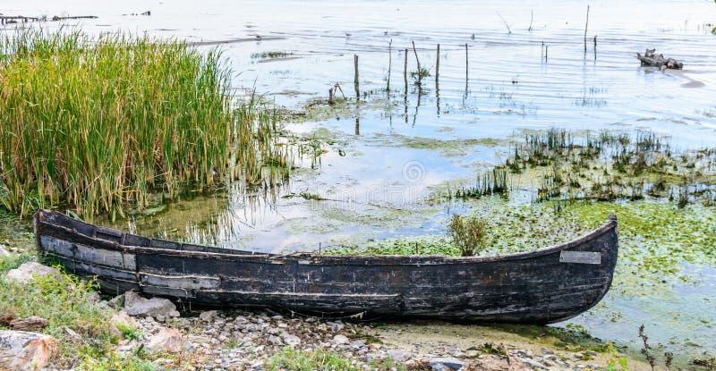 Stara łódź blisko brzeg z zielonym krzakiem Horyzontalny widok obraz stock