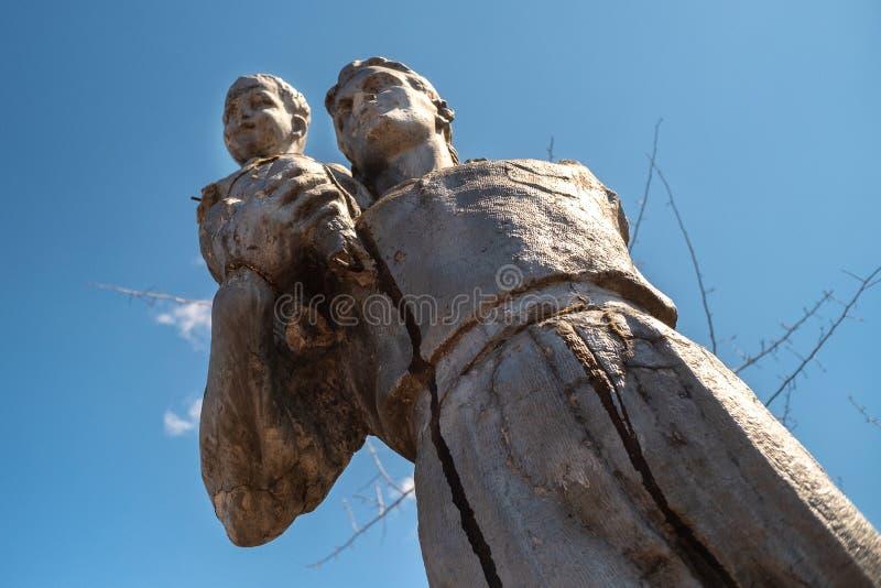 Stara łamająca pomnikowa rzeźba czasy USSR ojciec na jego ręka synu i obraz royalty free
