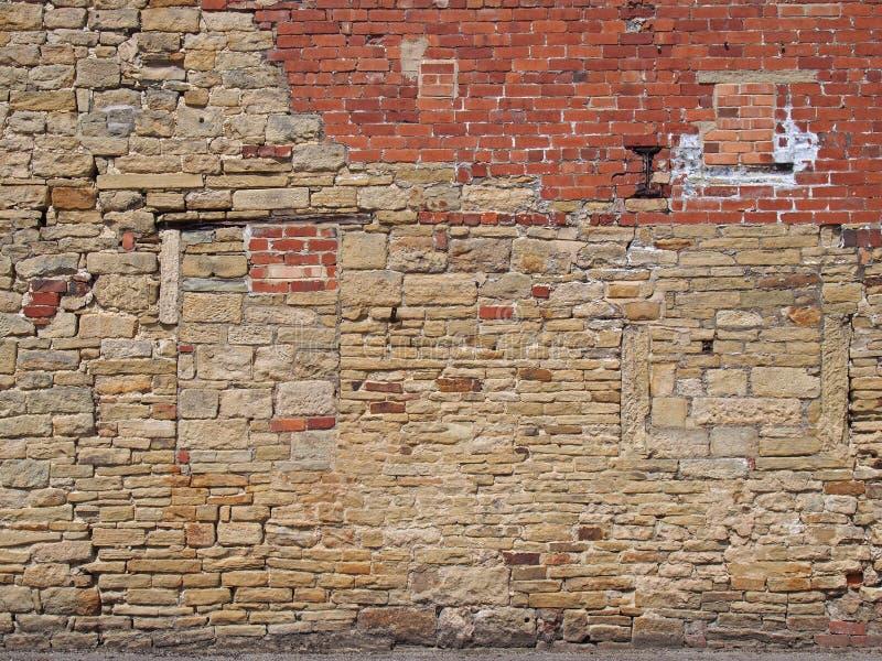 Stara ściana zewnętrzna z nieregularną łataną i naprawioną powierzchnią cegły i kamienia fotografia stock
