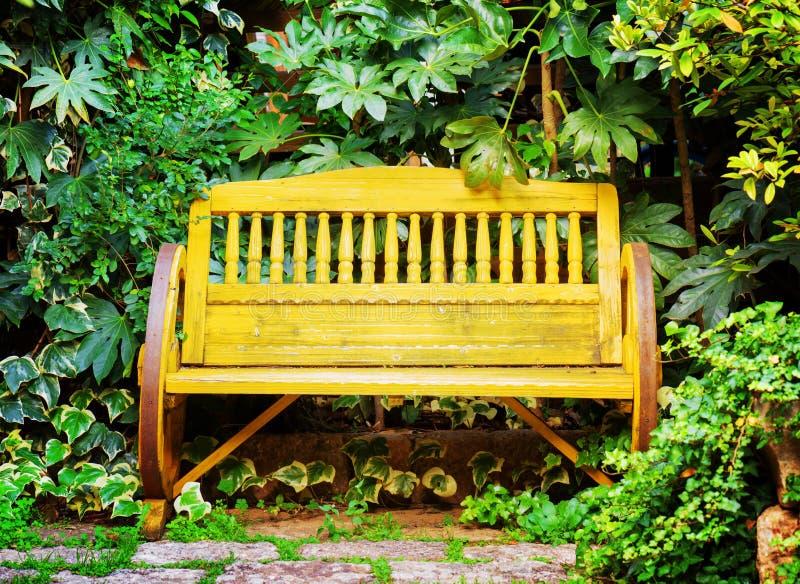 Stara żółta drewniana ławka w ogródzie ilustracyjny lelui czerwieni stylu rocznik fotografia stock