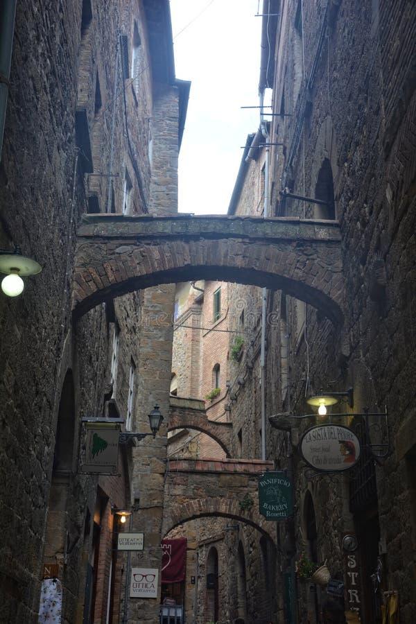 Stara aleja w starym miasteczku Volterra w Włochy z kamienia łukiem zdjęcia royalty free