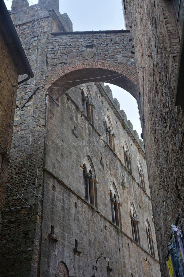 Stara aleja w starym miasteczku Volterra w Włochy z kamienia łukiem fotografia royalty free