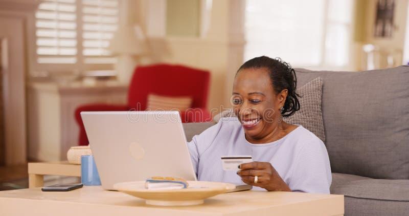 Stara amerykanin afrykańskiego pochodzenia kobieta używa kredytową kartę robić niektóre online zakupy laptop i obraz stock