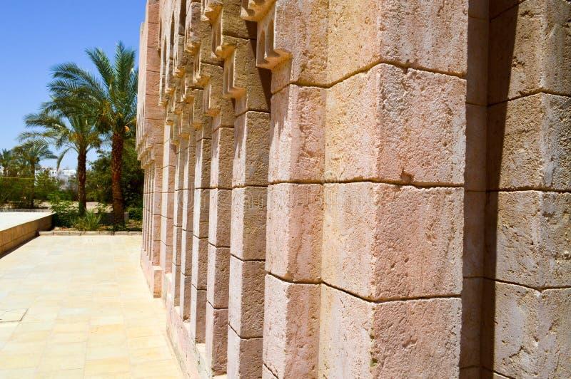 stara antyczna rzeźbiąca Arabska Islamska Islamska ściana z ornamentami i wzorami przeciw tłu zieleni tropikalni drzewka palmowe  zdjęcia stock