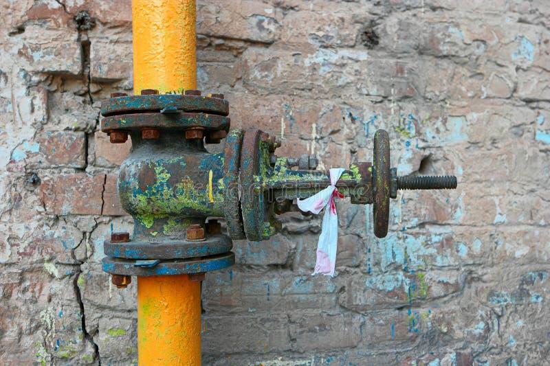Stara benzynowa drymba malująca w kolor żółty fajczanej i ośniedziałej klapie z punktami przestarzała farba przy ściana z cegieł zdjęcia royalty free
