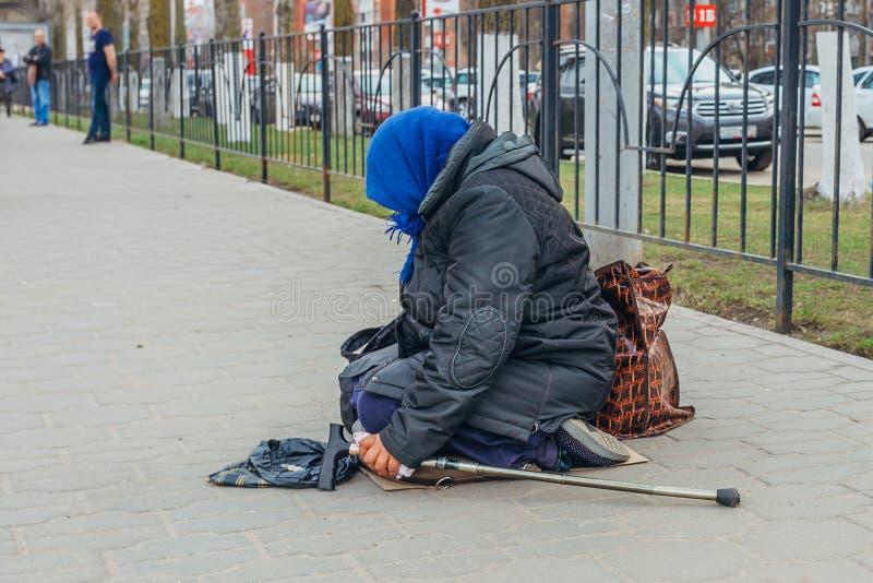 Stara bezdomna kobieta siedzi na ulicznym i proszałnym pieniądze zdjęcia stock