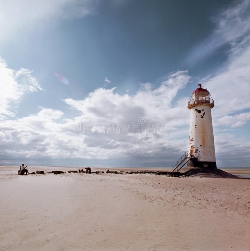Stara biała latarnia morska z czerwonym dachem na i niebem w tle piaskowatej plaży i droga przemian w przodzie z morzem zdjęcia stock