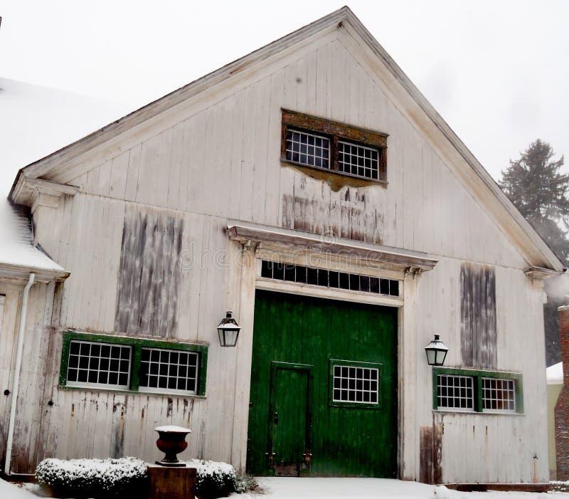 Stara brudna biała Nowa Anglia stajnia z zielonymi drzwiami i panel drzwiami fotografia royalty free