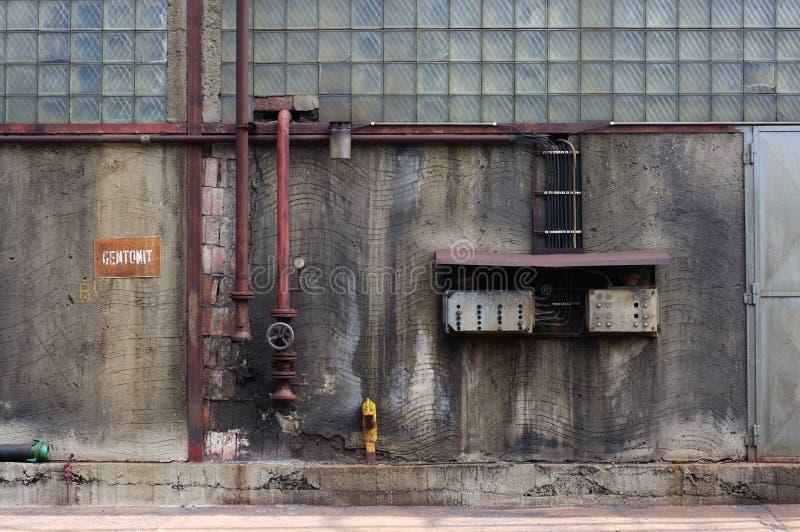 Stara brudna fabryki ściana z drymbami i elektryczności centralą zdjęcia stock