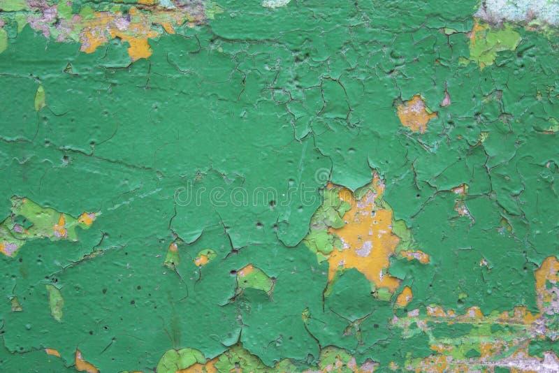 Stara brudna podława zieleni ściana z pęknięciami, narysami i obieranie żółtą farbą, Szorstkiej powierzchni tekstura fotografia royalty free