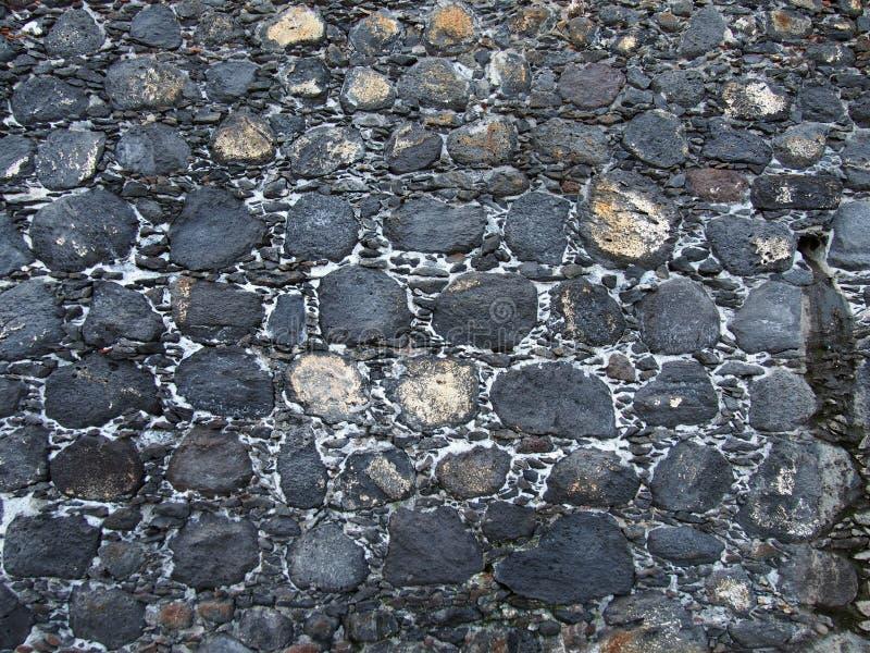 Stara czarna nieregularna wzorzysta kamienna ściana obrazy stock