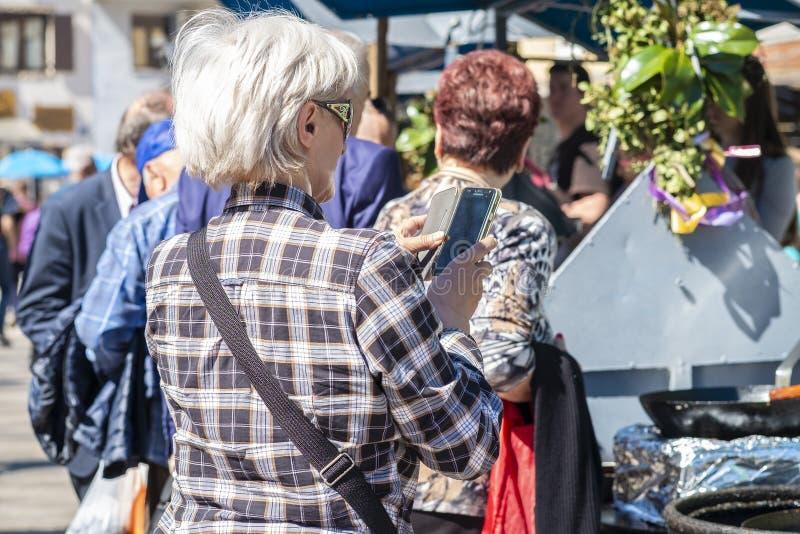 Stara dama bierze fotografie na jej telefonie komórkowym obrazy royalty free