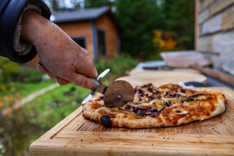 Stara dama ciie pizzę która właśnie wynikał plenerowego chlebowego piekarnika fotografia royalty free