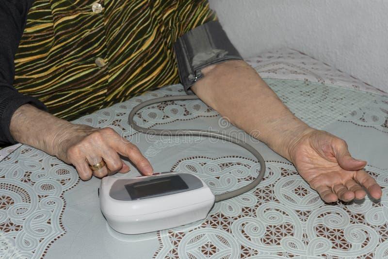 Stara dama sprawdza jej ciśnienie krwi obraz royalty free