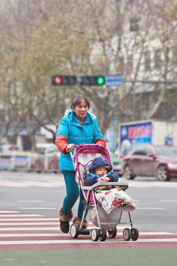 Stara dama z wnukiem w dziecko samochodzie, Yiwu, Chiny obraz royalty free