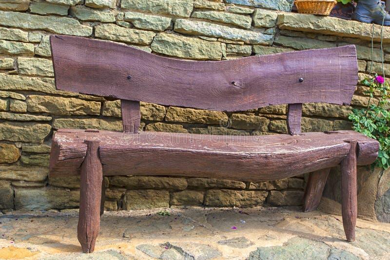 Stara drewniana ławka przy ścianą kamienny dom zdjęcia stock