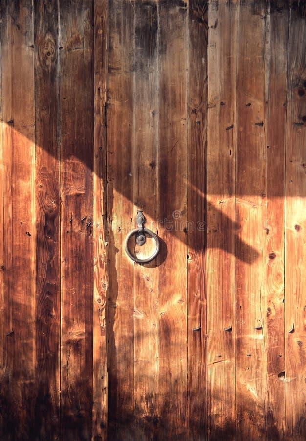Stara drewniana brama z metal drzwiową gałeczką Ringowa kształt rękojeść Zmrok - pomarańczowy drewniany tło obrazy stock