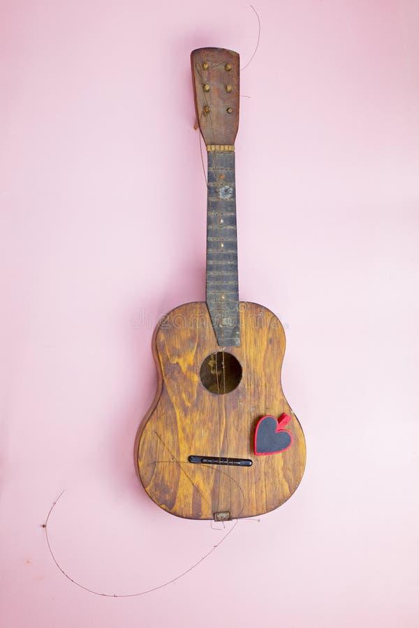 Stara drewniana gitara z poszarpanymi metali sznurkami obraz royalty free