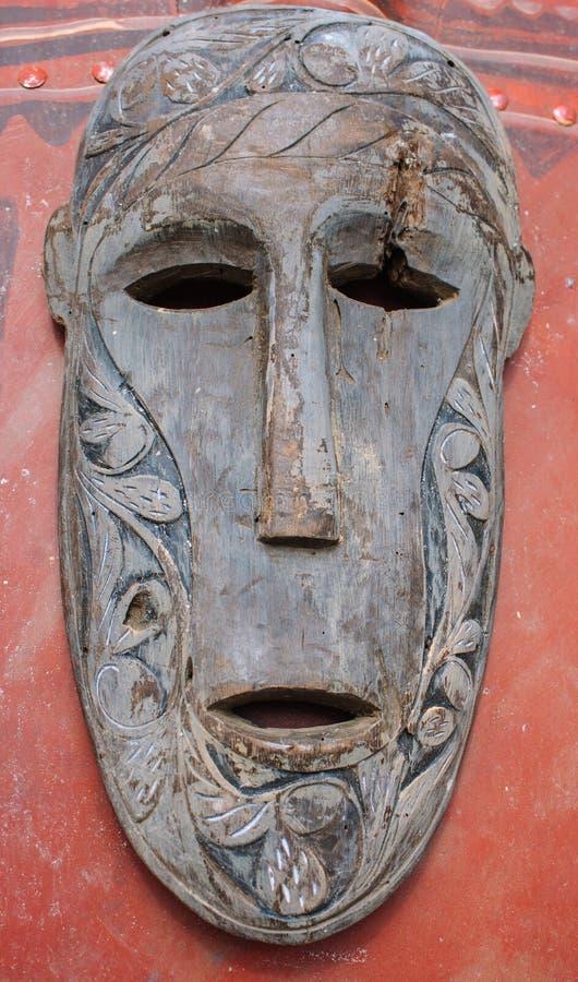 Stara drewniana maska na czerwonym sztandarze Spirytusowa twarz totem Azjatycka handmade rzeźba Obrządkowy przedmiot Religijna sz zdjęcie stock