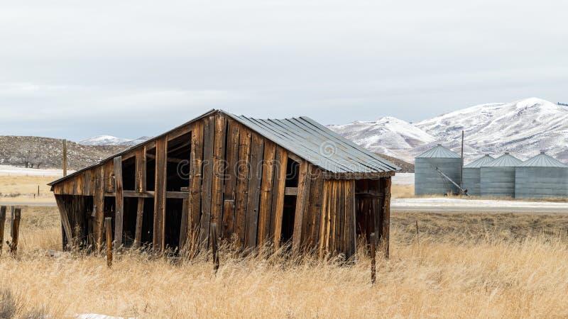 Stara drewniana rolnik jata na wiejskiej drodze w zimie zdjęcia stock