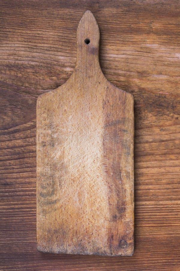 Stara drewniana tnąca deska na drewnianym tle zdjęcia royalty free