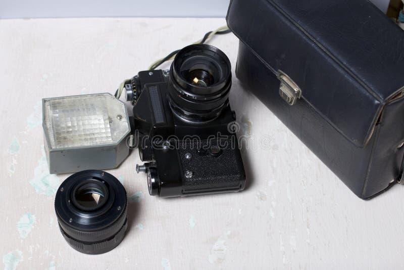Stara ekranowa kamera, usuwalny obiektyw i depeszujący błysk, Kłamają na powierzchni stół fotografia stock