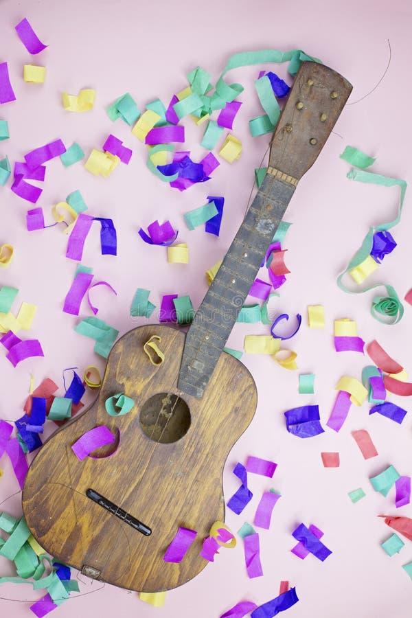 Stara gitara w barwiących confetti na różowym tle zdjęcia stock