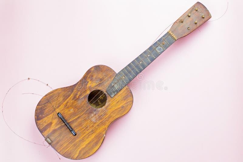Stara gitara z łamanymi sznurkami na różowym tle zdjęcia stock