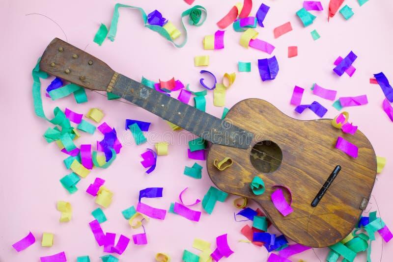 Stara gitara z poszarpanymi sznurkami w barwi?cych confetti na r??owym tle fotografia stock