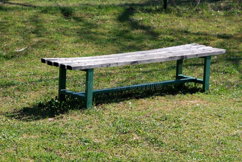 Stara jawna parkowa ławka z drewnianą siedzenia i zieleń metalu poparcia ramą otaczającą z świeżo ciącą trawą w miejscowego parku zdjęcia stock