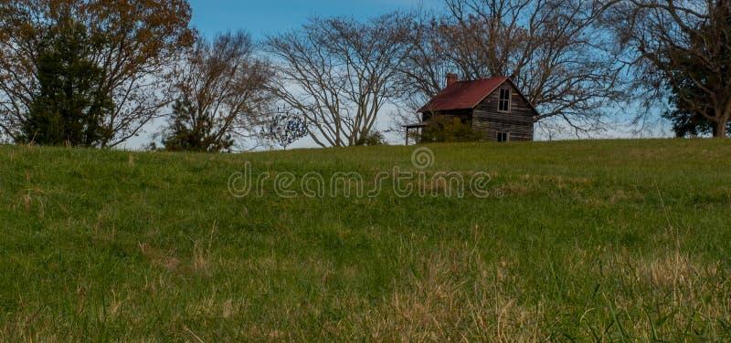 Stara kabina na wzgórzu pod drzewami zdjęcie stock