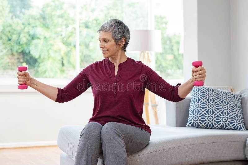 Stara kobieta ćwiczy z dumbbells fotografia stock