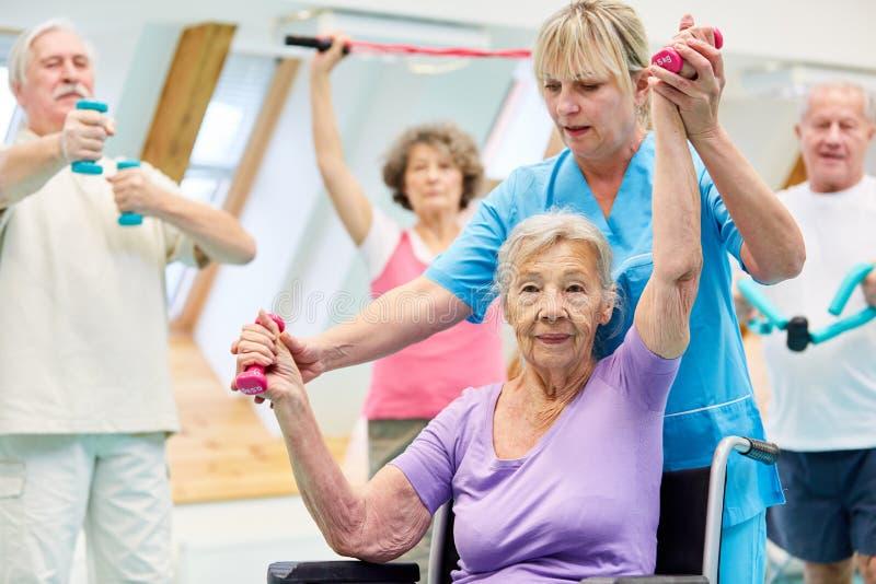 Stara kobieta ćwiczy z dumbbells w rehab klasie fotografia royalty free
