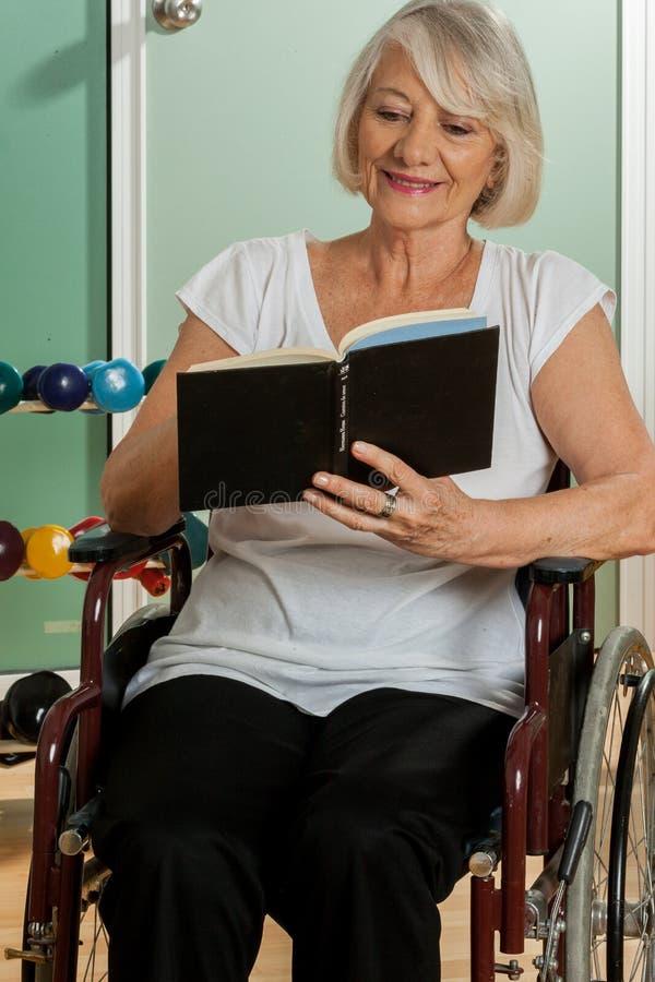 Stara kobieta czyta książkę w wózku inwalidzkim zdjęcia royalty free